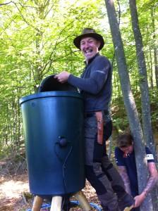 """Glada miner när Michael fyller på fodertunnan och Emanuel håller gamla tunnan som fungerar som """"stege"""" vid monteringen. Foto:LPR"""