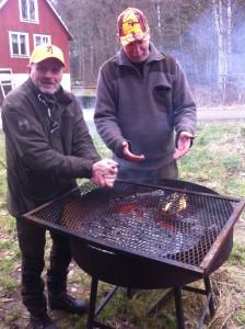 Stefan Lilja och Molles husse Mikael värmer sig vid ankomst till grill-platsen.